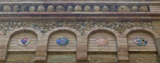 Detall de la decoració de la façana amb còdols de riu i arcs cecs.