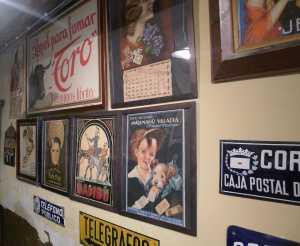 Cartells a la paret de l'estanc on es pot veure l'anunci d'un nen amb un cigarret a la boca.