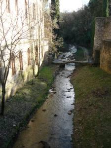 El riu Galligants. A l'esquerra el mur del monestir.