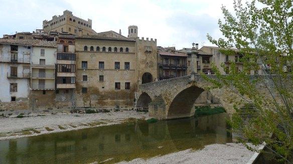 Pont de pedra amb la porta de Sant Roc i, sobressortint, el castell i el campanar.