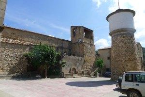 Plaça major amb el lateral de l'església i la torre d'aigües.