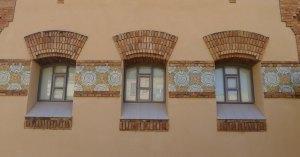 Detall de finestres i ceràmica en una façana.