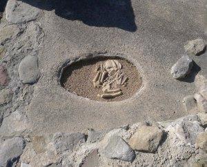 Reproducció d'un enterrament infantil en un dels edificis del jaciment.